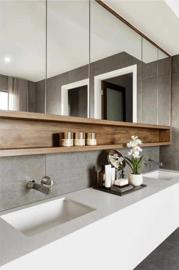 Close-up of white bathroom vanity with concrete splashback and timber cabinetry