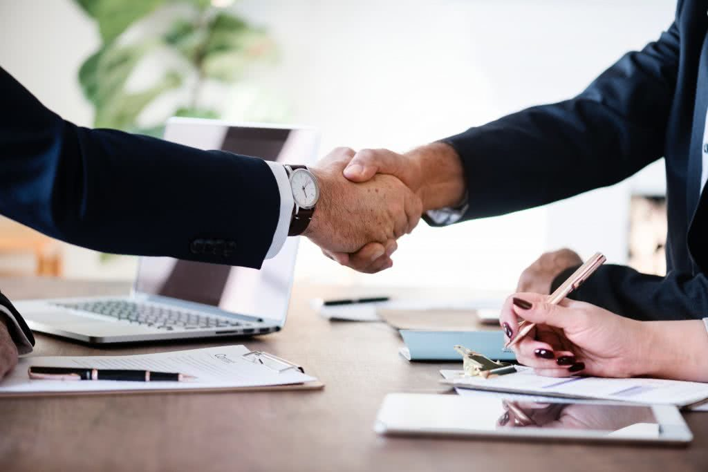 Solicitor shaking hands with buyer with contract on desk underneath