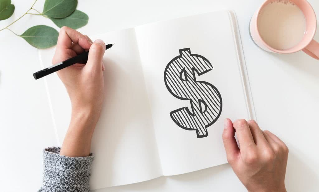 Woman drawing a dollar symbol, evaluating mortgage options