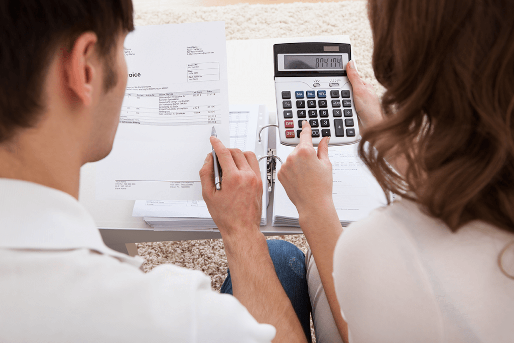 Couple reviewing finances, calculating budget for first home