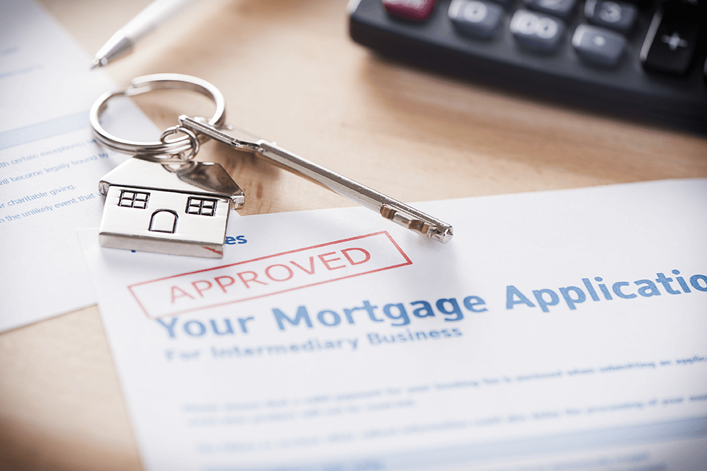Mortgage application with red approved stamp, keys to new home beside it